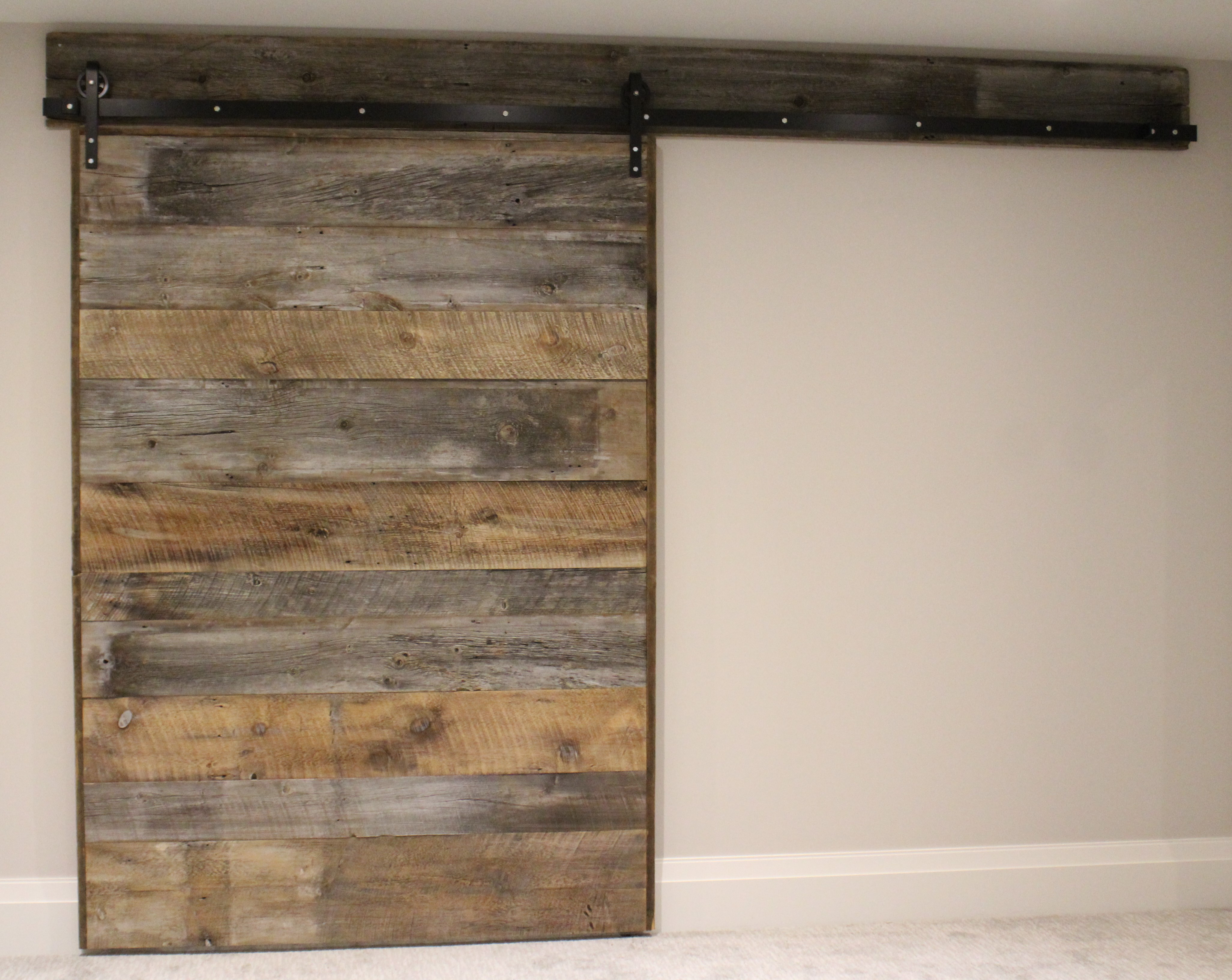 A rustic barn door in forrest hill rebarn toronto for Rustic hardware barn doors